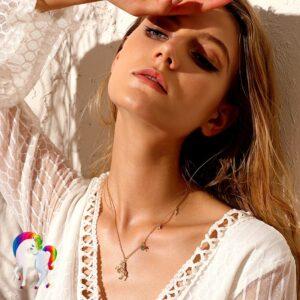 Une jeune femme la tête en arrière qui porte un Collier de larme de licorne a son cou vu de prêt