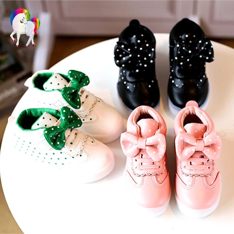 Baskets lumineuses pour filles rose, blanche, noir sur une table vue de prêt