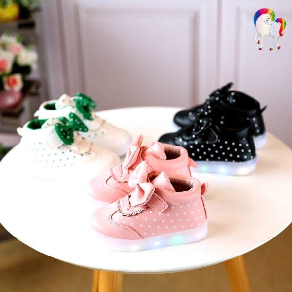 Baskets lumineuses pour filles rose, blanche, noir sur une table